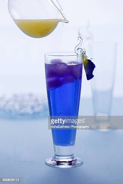 Pouring lemon juice on Butterfly pea drink