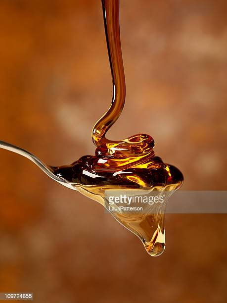 pouring maple syrup over a spoon - syrup stock pictures, royalty-free photos & images