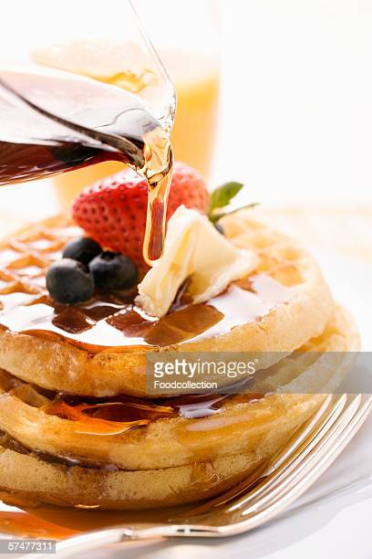 Pouring maple syrup over waffles with butter & berries