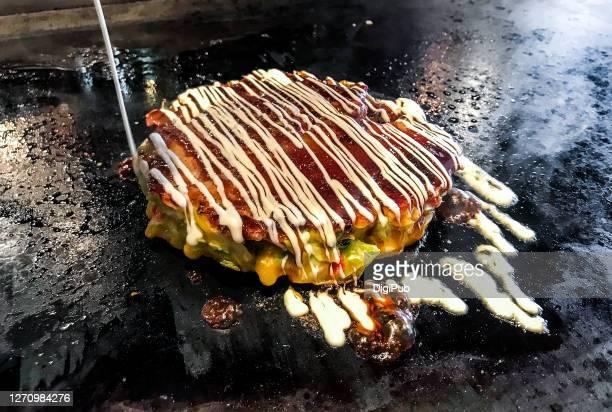 pouring mayonnaise on okonomiyaki - okonomiyaki stock pictures, royalty-free photos & images