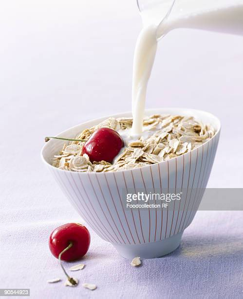 Pouring milk into oat flakes, close up