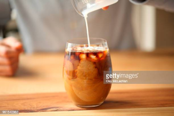 Pouring milk to glass with coffee, Oakland, USA
