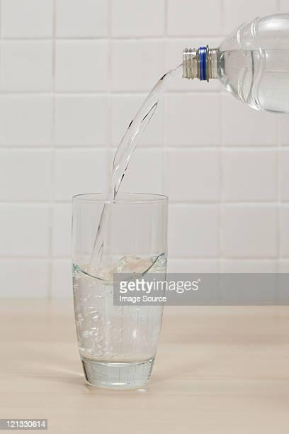 Verter agua mineral en vidrio