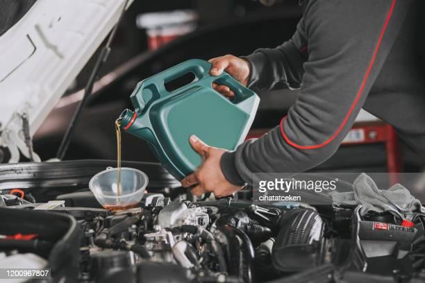 pouring oil to car engine. - óleo imagens e fotografias de stock