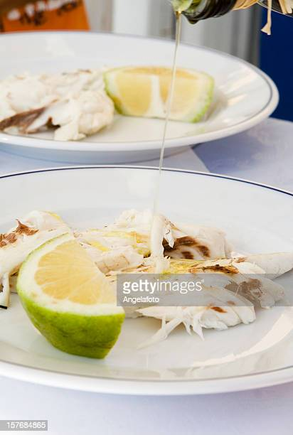 pouring olive oil down to roasted fish - extra virgin olive oil stock pictures, royalty-free photos & images