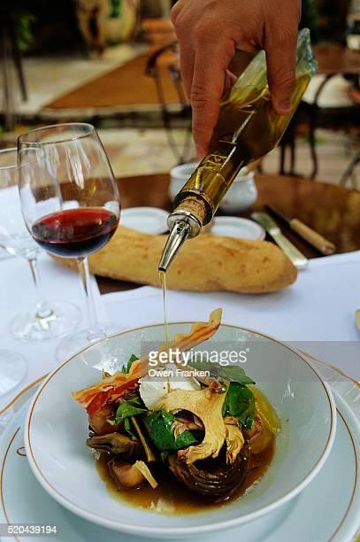 pouring olive oil on artichoke barigoule - アルプドオートプロバンス県 ストックフォトと画像