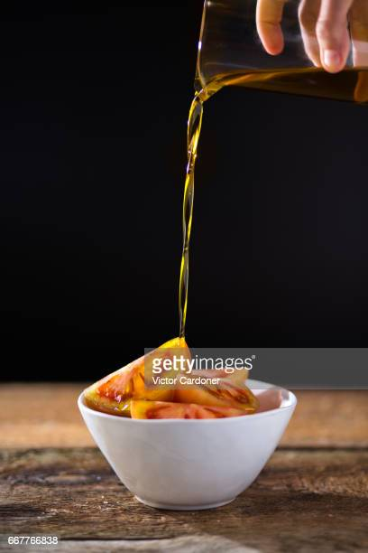 pouring olive oil on tomato salad - extra virgin olive oil stock pictures, royalty-free photos & images