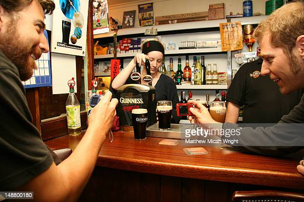 pouring pints of guinness at pub. - guinness stock pictures, royalty-free photos & images