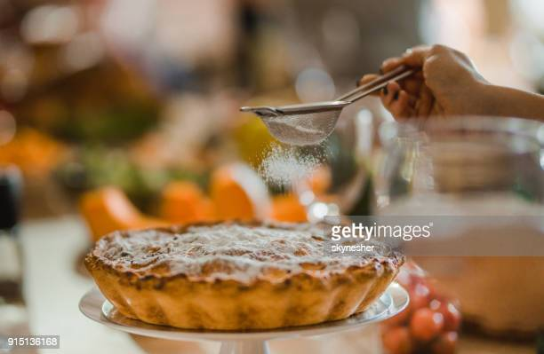 pouring powdered sugar on apple pie! - savory pie stock photos and pictures