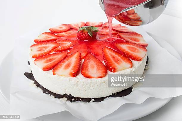Pouring red cake glaze on strawberry cream cheese tart