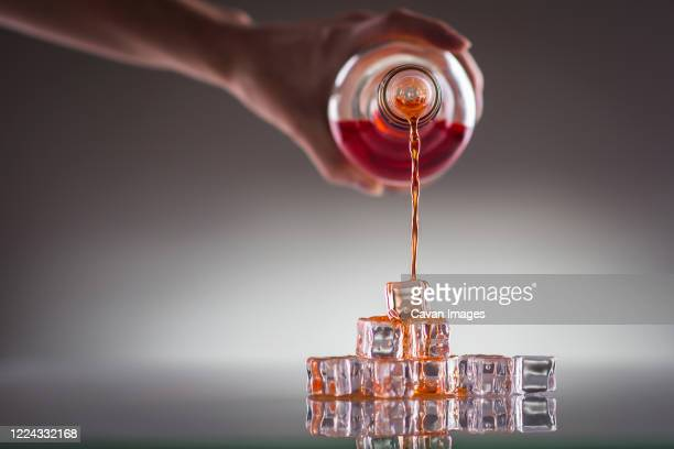 pouring red drink over ice cubes; mixing drinks- conceptual image - volume fluid capacity stock pictures, royalty-free photos & images