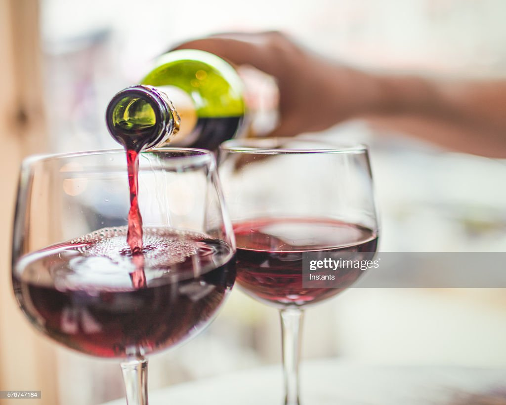 Pouring red wine in glasses : Stock Photo