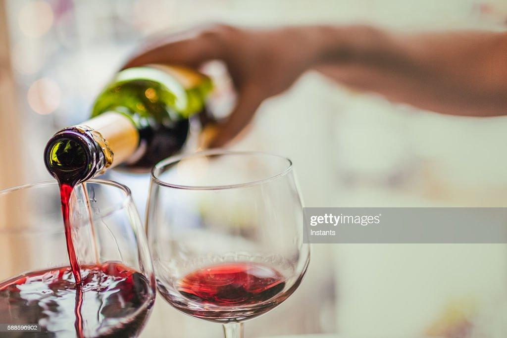 Pouring red wine in glasses : Foto de stock