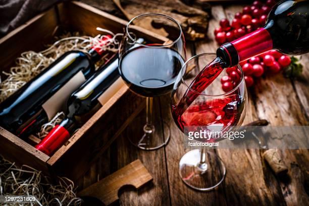 het gieten van rode wijn in een glas op rustieke houten lijst - wijnfles stockfoto's en -beelden