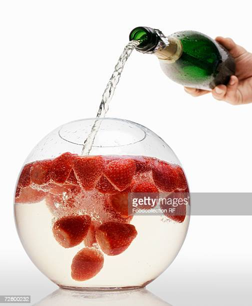 Pouring sparkling wine into strawberry punch