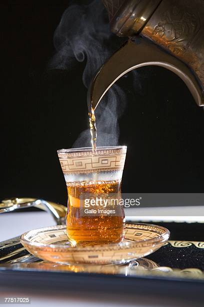 Pouring Steamy Hot Tea with Dallah into Cup. Dubai, United Arab Emirates