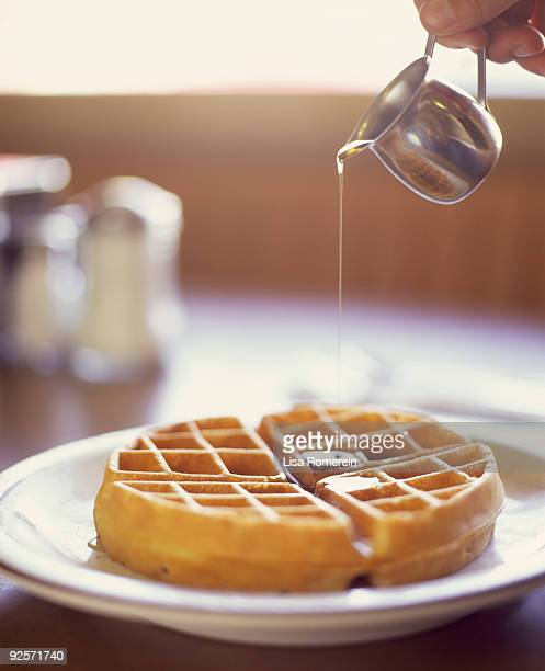 Pouring syrup on waffle