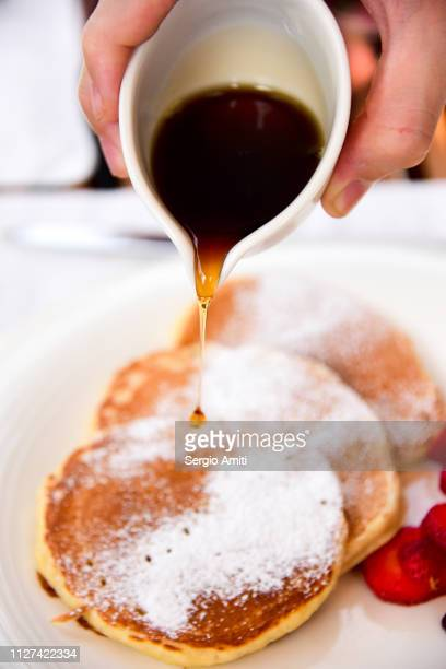 Pouring syrup over pancakes