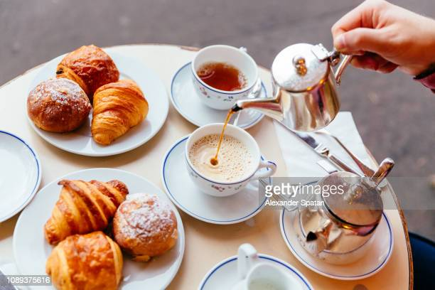 pouring tea in the cup while having breakfast at sidewalk cafe - french culture stock pictures, royalty-free photos & images