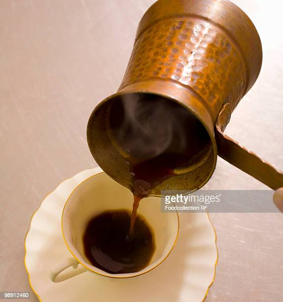 Pouring Turkish coffee into cup, elevated view, close-up