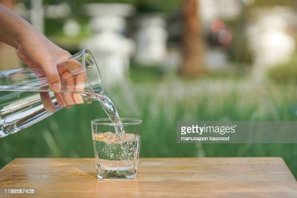 pouring water from bottle into glass. - natural condition stock pictures, royalty-free photos & images
