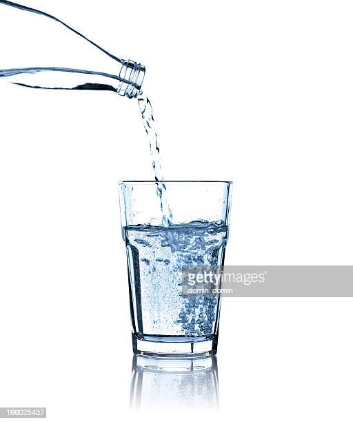 pouring water from bottle into glass, studio shot, isolated - drinking glass stock pictures, royalty-free photos & images