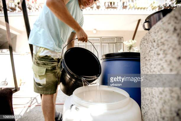 pouring water from bucket - bucket stock pictures, royalty-free photos & images