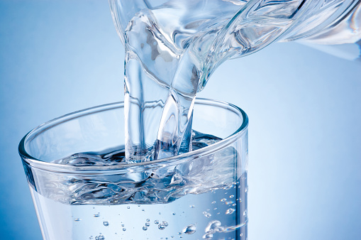Pouring water from jug into glass on blue background 1152418742