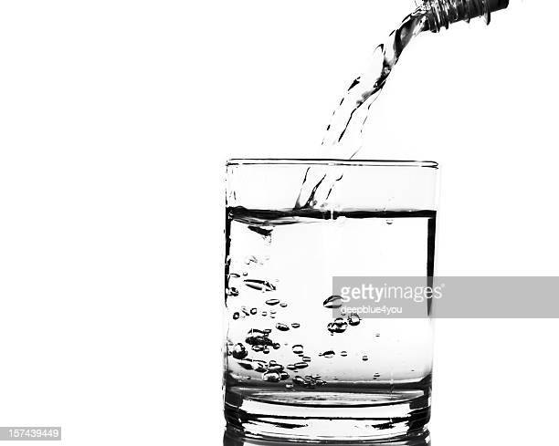 Pouring water into a glass on white