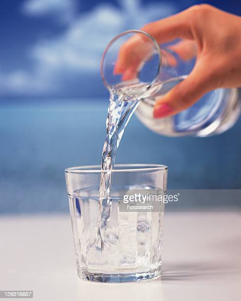 Pouring Water into Glass from Pitcher, Close Up, Differential Focus, In Focus, Out Focus, Side View