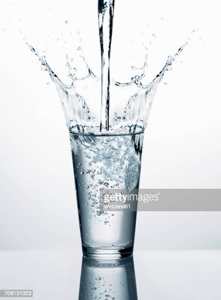 Pouring water into glass in front of white background