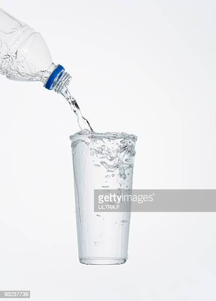 Pouring water out of a bottle into a glass.
