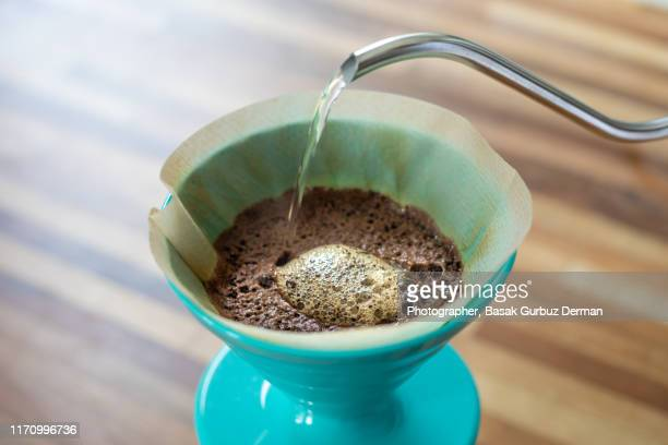 Pouring water with a rotating movement on the coffee grounds  to wet them evenly, this step is called bloom