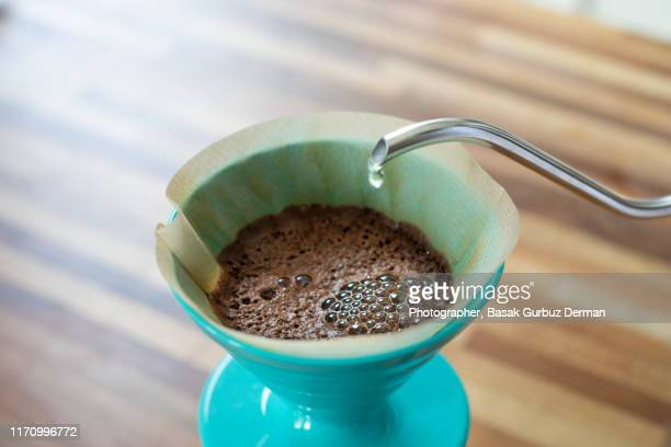 pouring water with a rotating movement on the coffee grounds  to wet them evenly, this step is called bloom - café moulu photos et images de collection