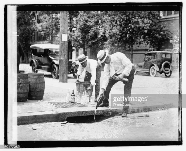 Pouring whiskey into a sewer during Prohibition 1920s