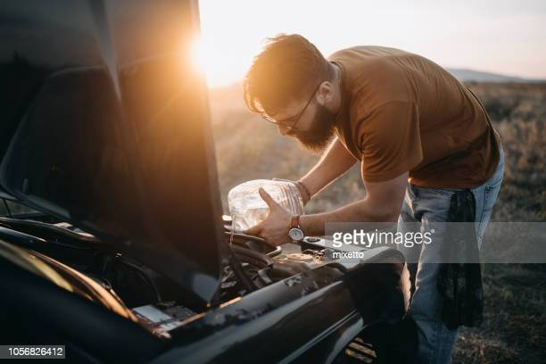 pouring windscreen washer - vintage auto repair stock pictures, royalty-free photos & images