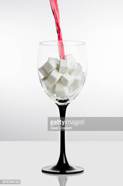 Pouring wine into glass full of sugar cubes