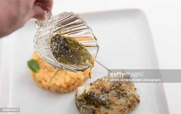 Pouring za'atar-wu-zayt sauce on codfish dish.