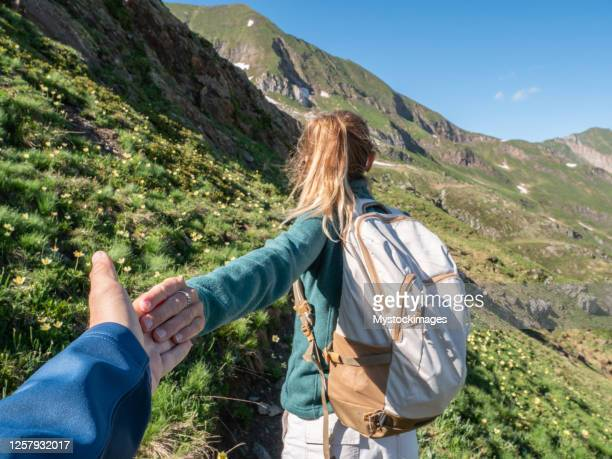 pov of couple holding hands, woman leading boyfriend to alpine lake - following stock pictures, royalty-free photos & images