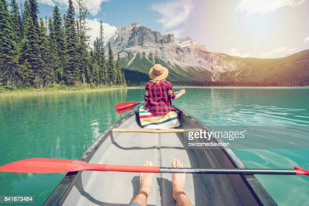 pov of couple paddling red canoe on turquoise lake - traditionally canadian stock pictures, royalty-free photos & images