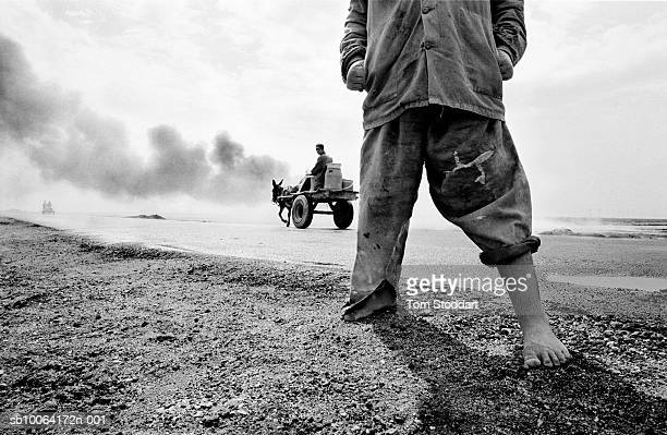 , Poverty in Southern Iraq, as a barefoot boy in rags is pictured next to a burning oil well near Basrah.
