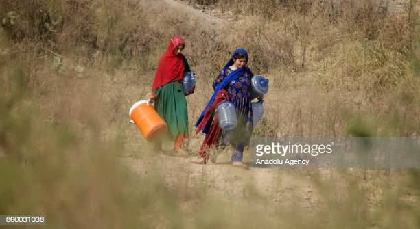 Povertystricken Afghan refugee girls make their way to bring drinking water from a water hand pump at an Afghan Refugee village on the International...