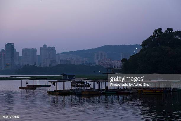 Powai lake at Mumbai with boats and urban skyline in background