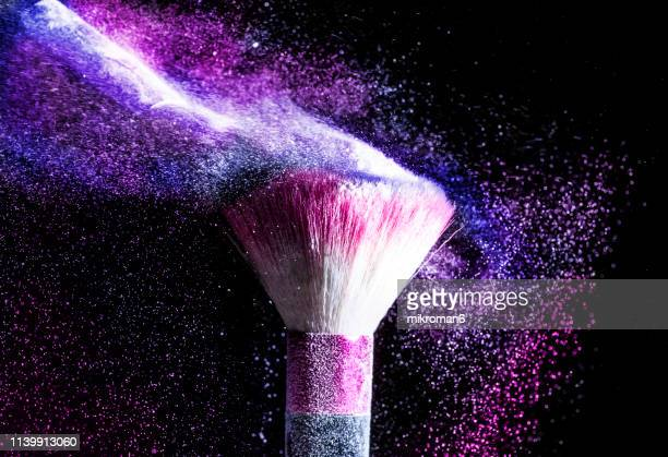 powder blowing from makeup brushes - stage make up stock photos and pictures