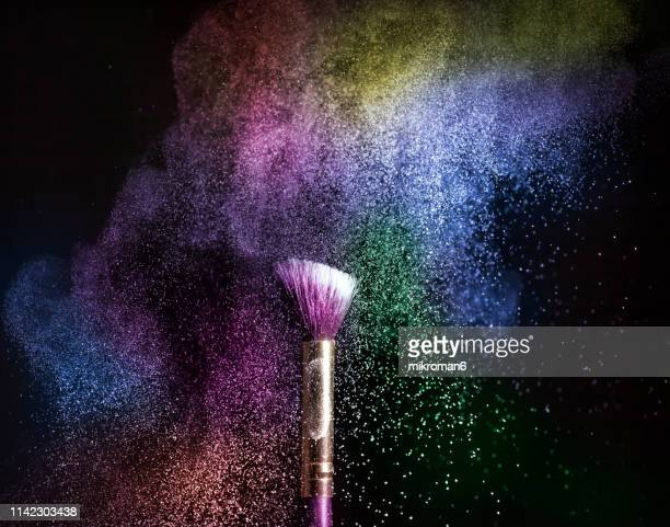 powder blowing from makeup brushes - body paint stock pictures, royalty-free photos & images