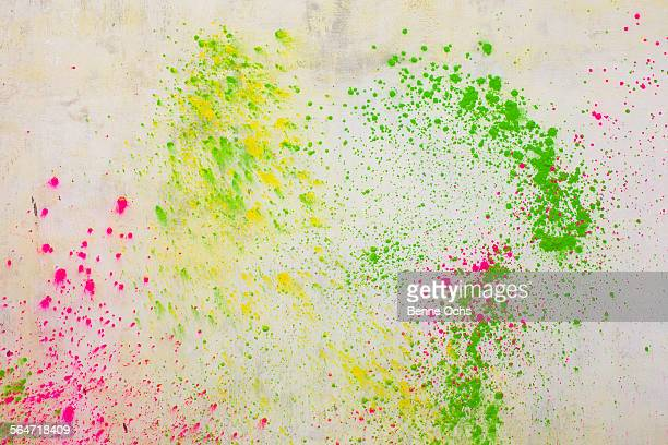 Powder paints spread on white wall during Holi festival