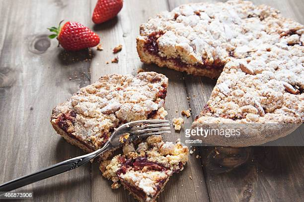 Powdered sugar strawberry tart on wooden kitchen table