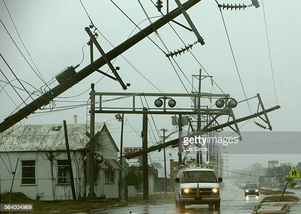 A power company truck drives under broken power poles in the wake of Hurricane Rita which hit hard in Lake Charles La High winds and heavy rains...
