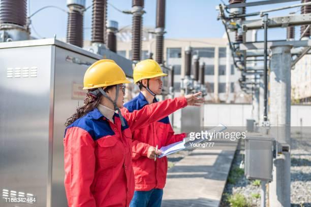 変電所の電気機器をチェックするパワーエンジニア - 工業設備 ストックフォトと画像