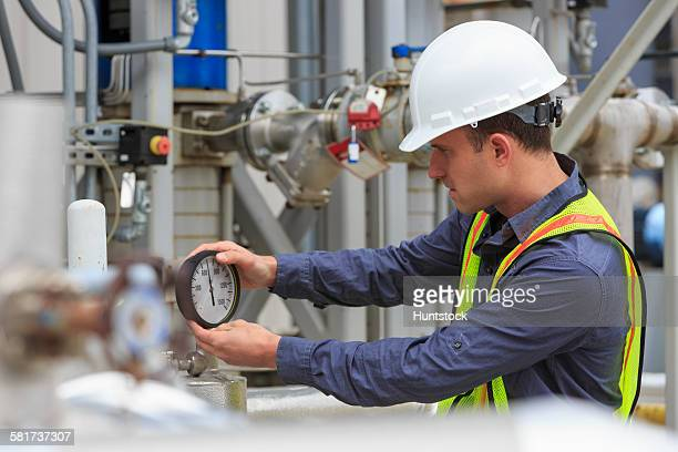 power engineer examining a gauge at a power plant - pressure gauge stock photos and pictures